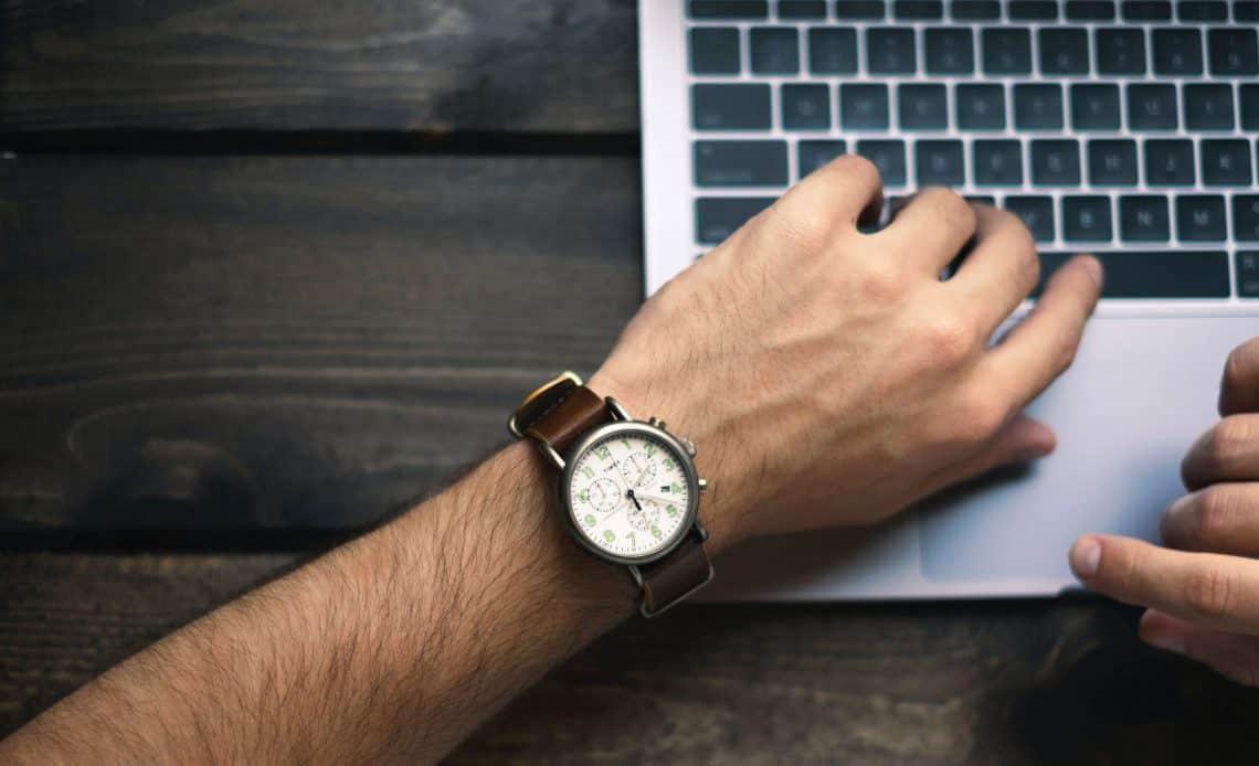 Dłoń z zegarkiem przy laptopie