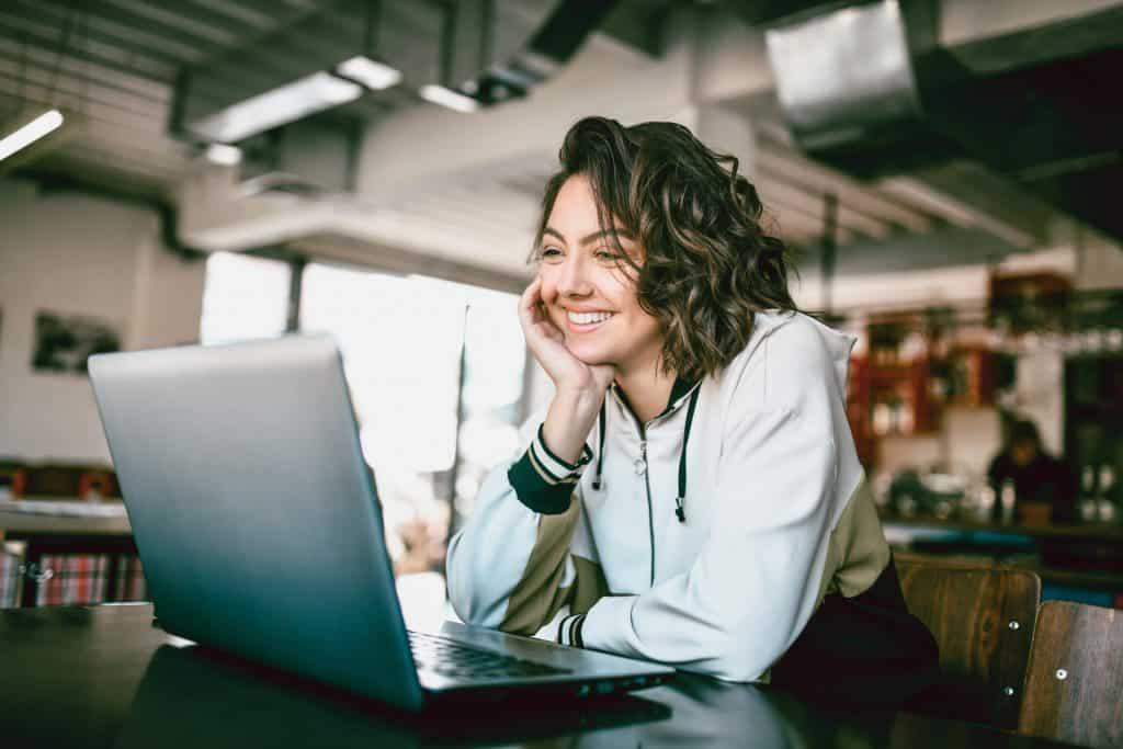 Uśmiechnięta kobieta siedzi przed laptopem